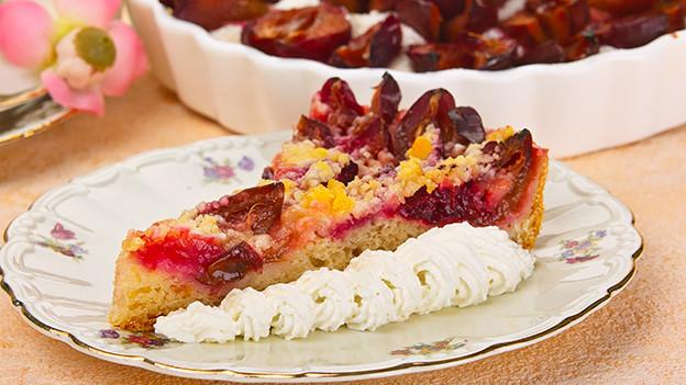 Ein Stück Zwetschenkuchen, mit Sahne dekoriert.