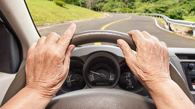Hände einer älteren Frau am Steuerrad.