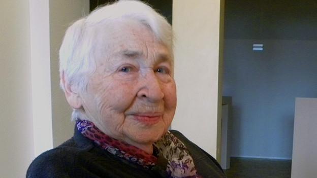 Eine weisshaarige Seniorin in einem Wohnzimmer.