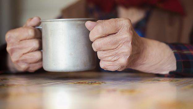 Zwei alte Hände halten eine Metalltasse.