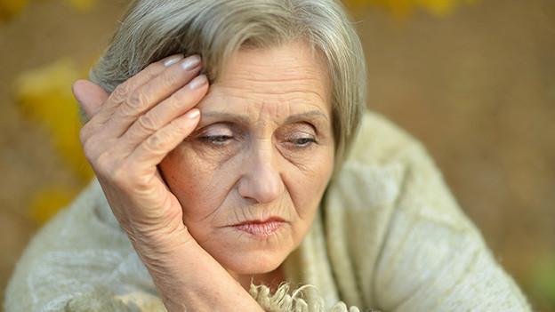 Eine ältere nachdenkliche Frau.
