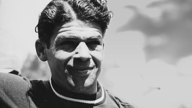 Schwarz-Weiss-Fotografie von einem jungen Mann mit dunklen Haaren.