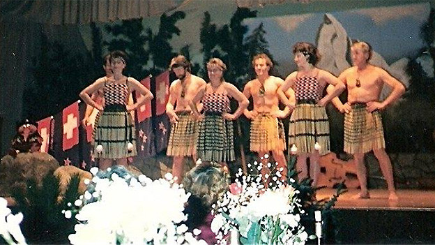 Die alte Fotografie zeigt Menschen in traditionellen Kleidern auf einer Bühne.