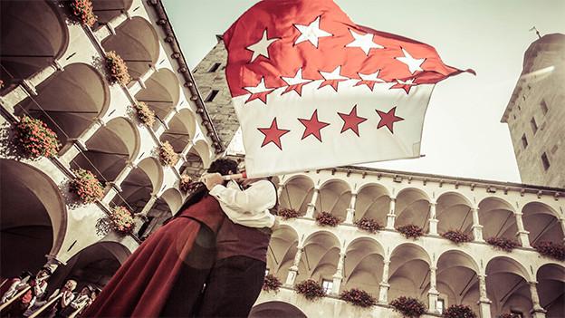 Eine Frau tanz mit einem Mann, der eine Walliser Kantonsfahne schwingt, in einem Schlosshof.