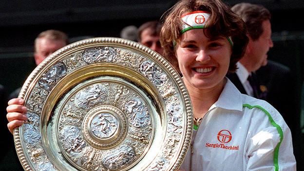 Eine junge Tennisspielerin zeigt stolz eine silbernen Präsentierteller.