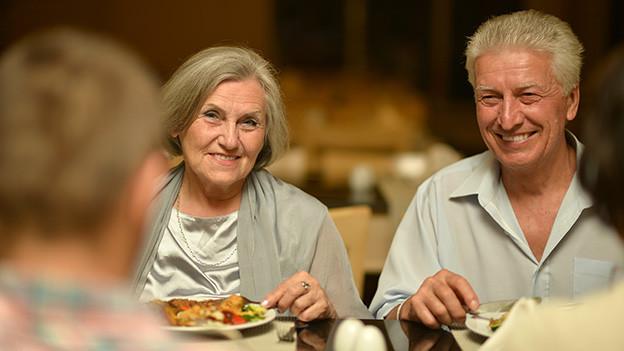Eine Gruppe von älteren Menschen sitzt beim Essen an einem Tisch im Restaurant.