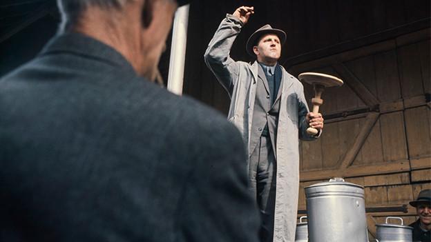 Ein Auktionator auf einem Bauernhof preist eine Milchkanne an.