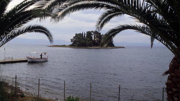 Zwischen Palmenblätter sieht man Meer und eine kleine Insel.