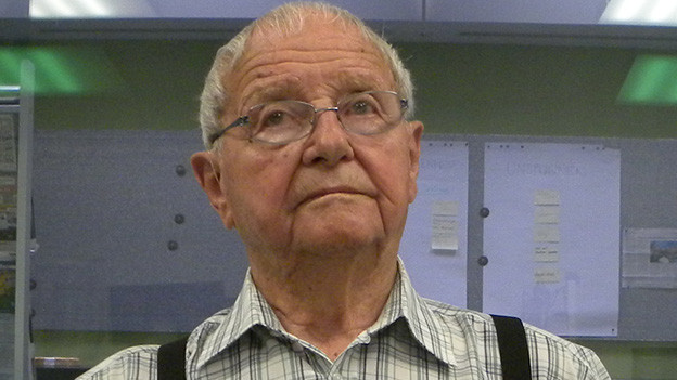 Ein ältere Mann mit Brille in einem Radiostudio.