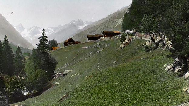 Blick auf eine paar Hütten hoch über einem Tal.