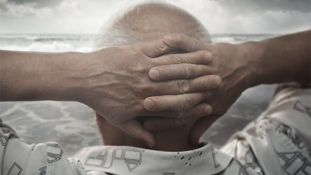 Ein Mann mit hinter dem Kopf verschränkten Händen blickt in die Weite.