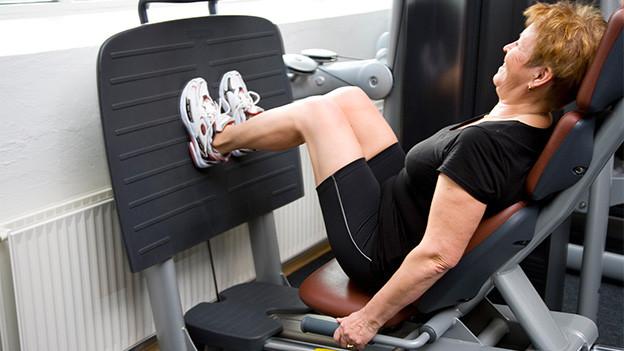 Eine ältere Frau an einem Gerät im Fitnesscenter.