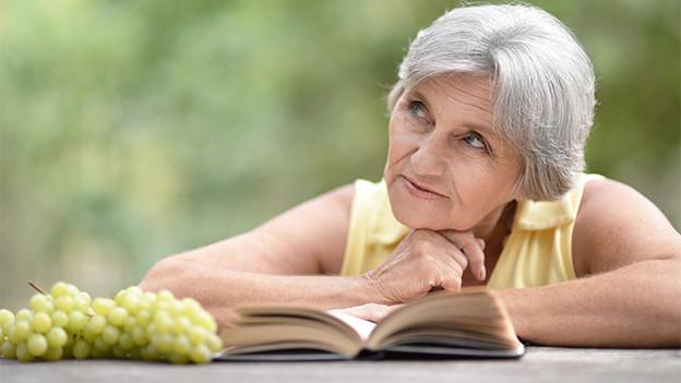 Eine ältere Frau sitzt nachdenklich an einem Tisch vor einem aufgeschlagenen Buch.