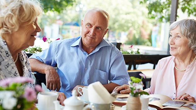 Ein Mann und zwei Frauen sitzen an einem gedeckten Tisch und unterhalten sich.