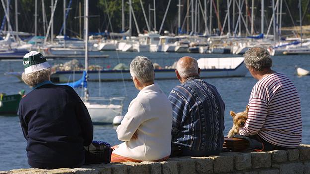 Vier ältere Männer und Frauen sitzen auf einer Hafenmauer und blicken in die Ferne.