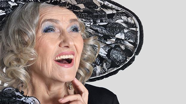 Eine ältere geschminkte Frau mit grossem Hut.