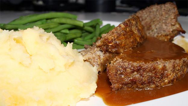 Ein Teller mit Kartoffelstock, Fleisch und grünen Bohnen.