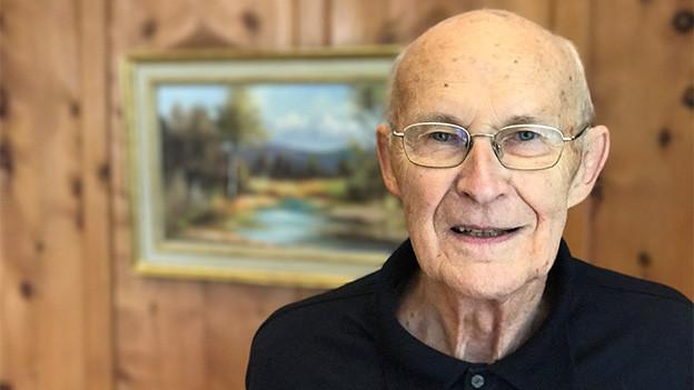 Ein älterer Mann mit Brille steht vor einer Holzwand, an der ein Bild hängt.