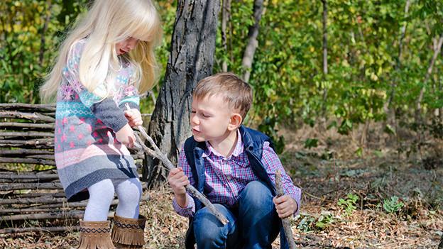 Ein Mädchen und ein Knabe spielen im Wald mit Holzstöcken.