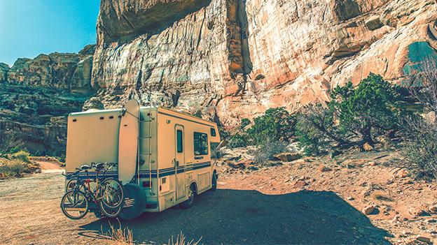 Ein Wohnmobil vor einer Felswand.
