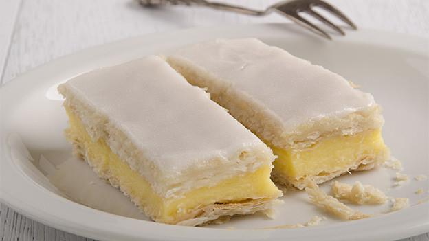 Zwei Crèmeschnitten auf einem weissen Teller.