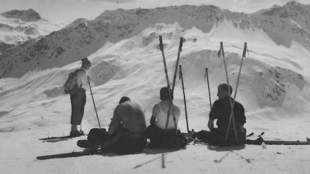 Eine Gruppe von Skifahrern sitzt im Schnee.