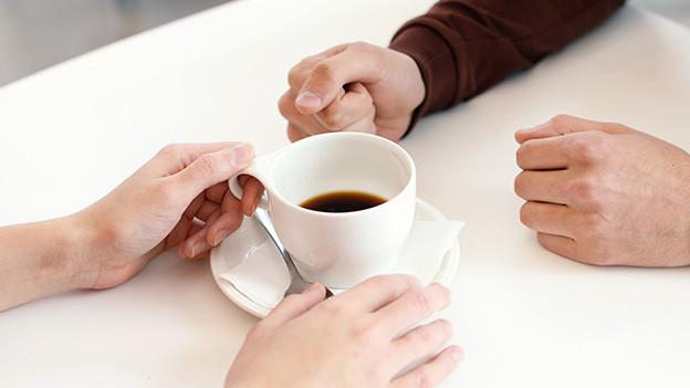 Vier Hände und eine Kaffeetasse auf einem Tisch.