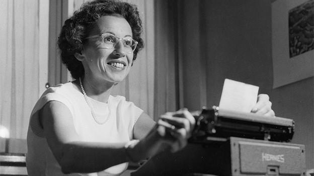 Schwarz-Weiss-Fotografie von eine dunkelhaarigen Frau bei der Arbeit im Büro.