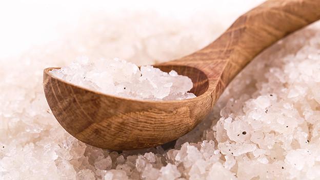 Grobe Salzkörner auf einem Holzlöffel.