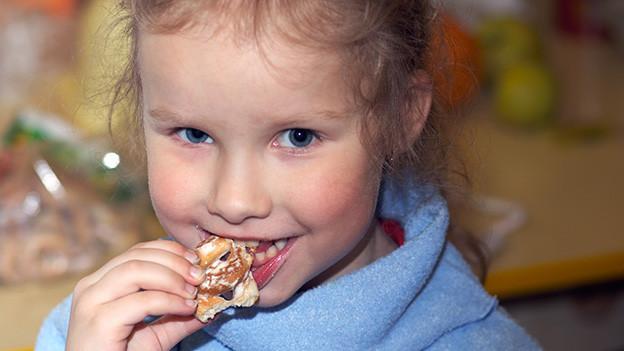 Ein kleines Mädchen isst strahlend einen Keks.