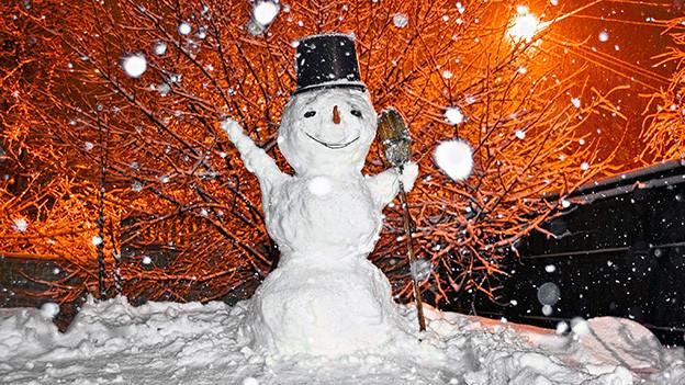 Es schneit grosse Flocken auf einen lachenden Schneemann.