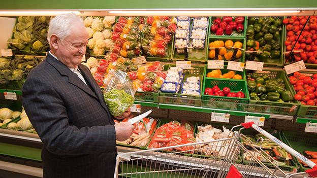 Ein ältere Mann steht in einem Lebensmittelgeschäft vor dem Früchte- und Gemüseregal.