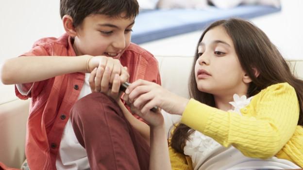 Zwei Kinder streiten sich um eine Fernbedienung.