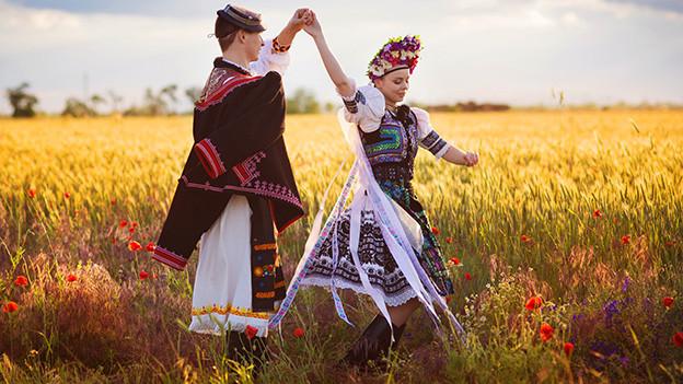 Ein junges farbig gekleidetes Paar tanz in einer Wiese.
