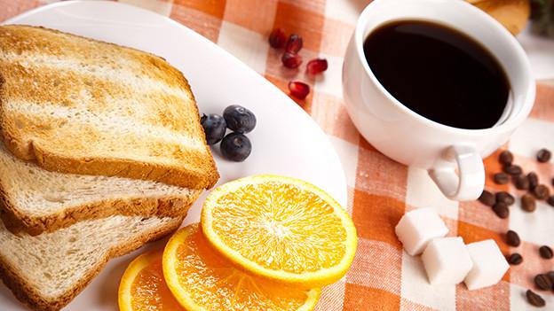Stillleben mit Toastbrotschreiben, einer Tasse Kaffe und Würfelzucker.