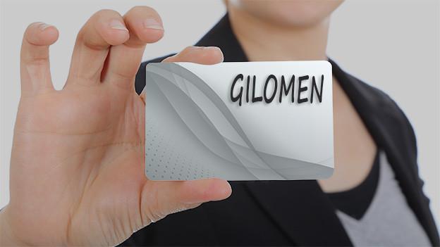 Konturen einer Frau, die eine Visitenkarte mit dem Namen Gilomen zeigt.