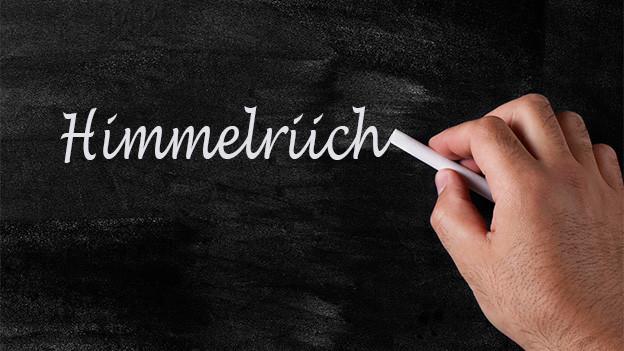 Jemand schreibt mit weisser Kreide das Wort «Himmelriich» auf eine Wandtafel.