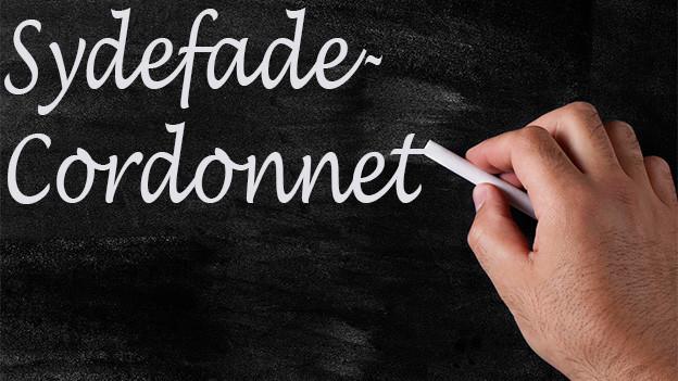 Jemand schreibt mit weisser Kreide das Wort «Sydefade-Cordonnet» auf eine Wandtafel.