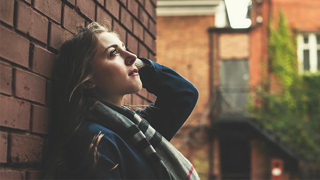 Eine junge Frau lehnt an einer Mauer und blickt sehnsüchtig in die Ferne.
