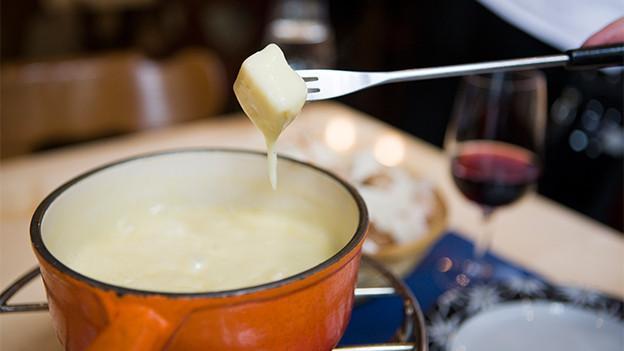 Eine Gabel mit einem kleinen Stück Brot über einem Caquelon mit Käsefondue.