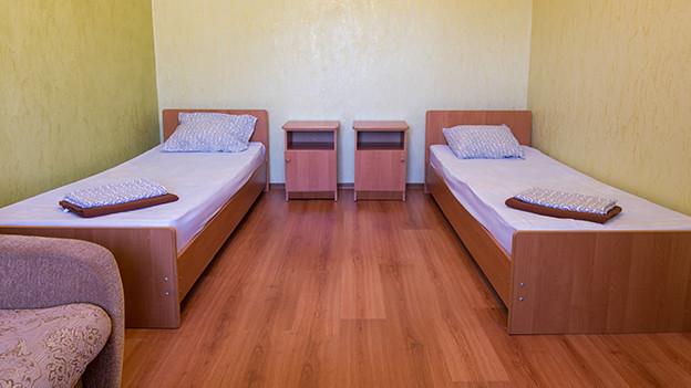 Zwei schmale Betten in einem einfachen Zimmer.