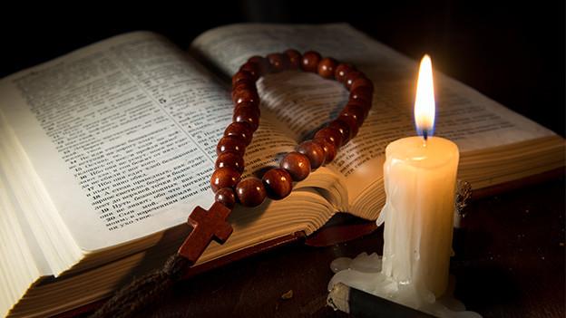 Eine Gebetskette auf einer Bibel im Kerzenlicht.
