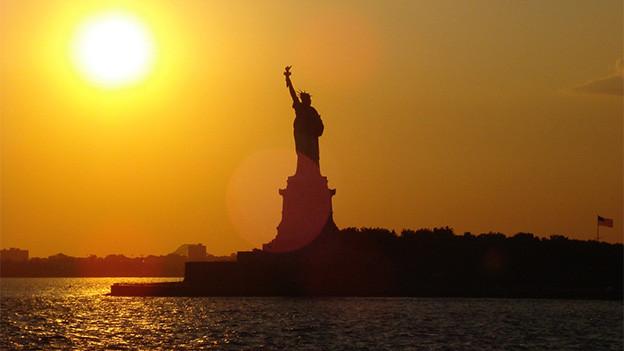 Die amerikanische Freiheitsstatue bei Sonnenuntergang.