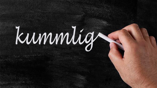 Jemand schreibt mit weisser Kreide das Wort «kummlig» auf eine Wandtafel.
