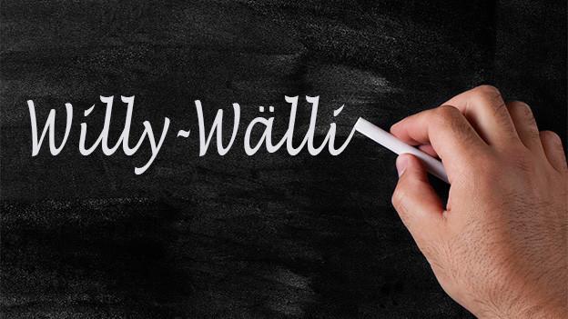 Jemand schreibt mit weisser Kreide das Wort «Willy-Wälli» auf eine Wandtafel.