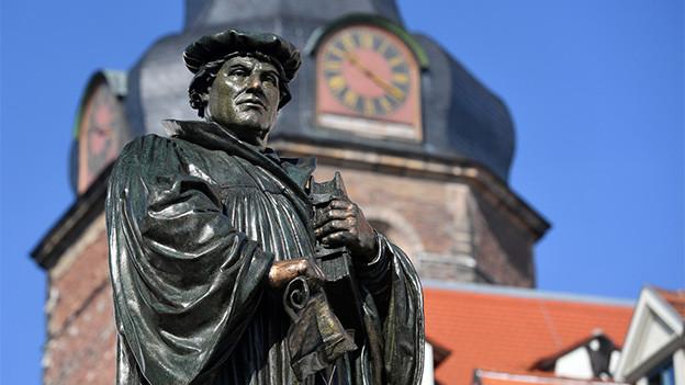 Ein Denkmal vor einer Kirche.