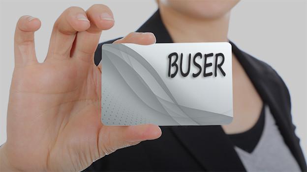 Konturen einer Frau, die eine Visitenkarte mit dem Namen Buser zeigt.