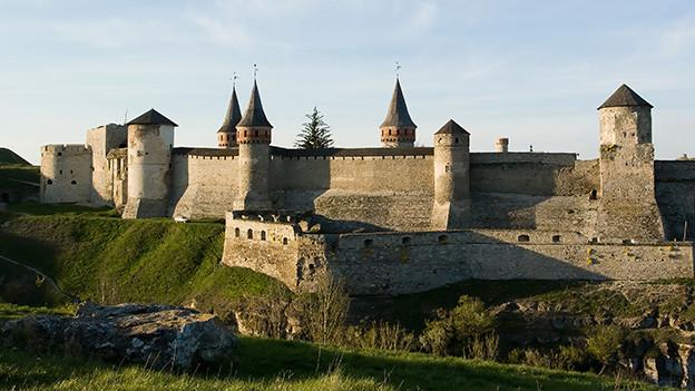 Blick auf eine Burg mit dicken Mauern und Türmen.