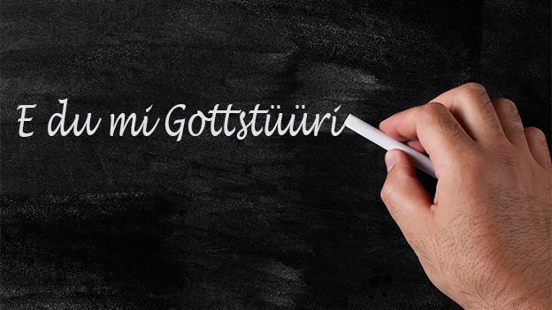 Jemand schreibt mit weisser Kreide den Ausdruck «E du mi Gottstüüri» auf eine Wandtafel.