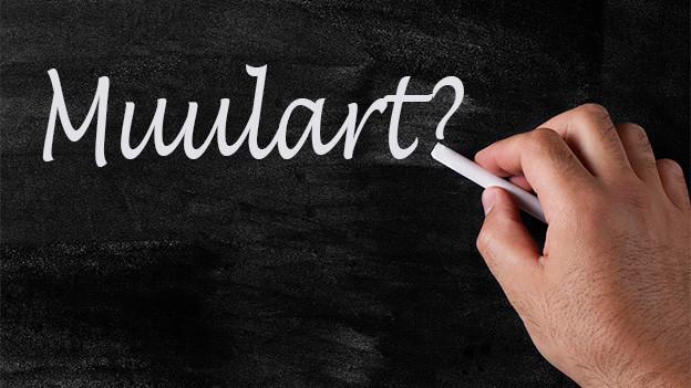 Jemand schreibt mit weisser Kreide das Wort «Muulart» auf eine Wandtafel.